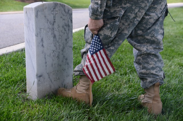 A Solider inserts a flag in front of a grave during the Flags-In ceremony at Arlington National Cemetery, Va., May 22, 2014.