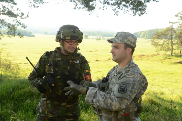 First Lt. David Ryan, commander of D Company, 1st Battalion, 167 Infantry Regiment, advises a member of the Romanian Army during a mission as part of Combined Resolve II, May 20, 2014, at Hohenfels, Germany.  Combined Resolve II is a U.S. Army Europe-directed multinational exercise at the Grafenwoehr and Hohenfels Training Areas, including more than 4,000 participants from 15 allied and partner countries. The exercise features the European Rotational Force, a combined arms battalion of the 1st Brigade Combat Team, 1st Cavalry Division, the U.S. Army's regionally-aligned rotational brigade combat team that supports the U.S. European Command for training and contingency missions.