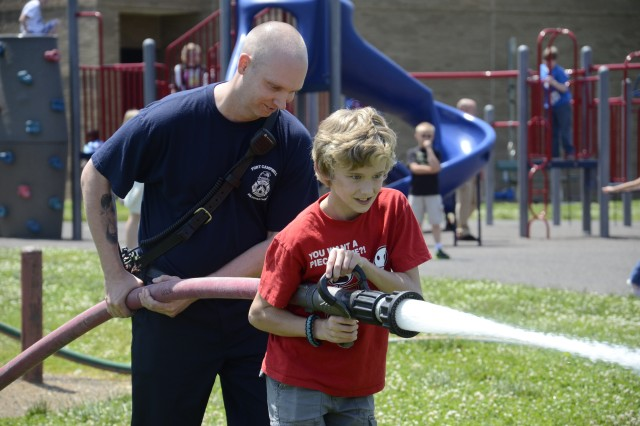 Nathan Liermann, a fifth grader at Andre Lucas Elementary School, gets some assistance advancing with the fire hose from Fort Campbell Fire Department's Paul Morgan, Monday afternoon. Getting the experience of spraying the fire hose was a part of the school's annual Firefighter Challenge.
