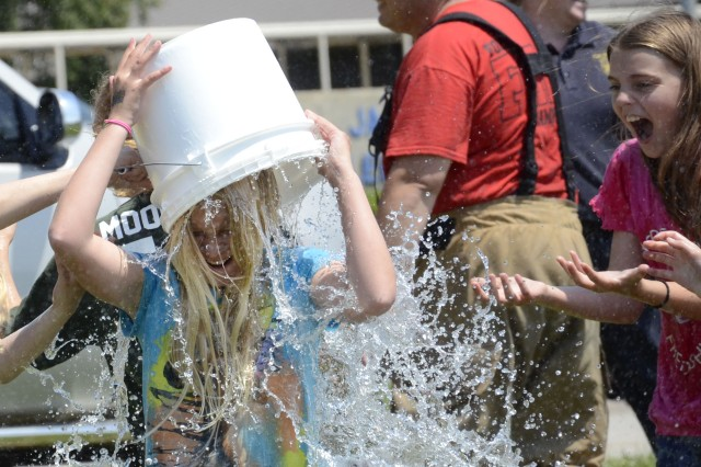 Fifth grader Desiree' Crouch pours water over her head at the conclusion of the Firefighter Challenge, while her friend Jordan Lamprides looks on. The challenge combined learning and end-of-year fun for the students.