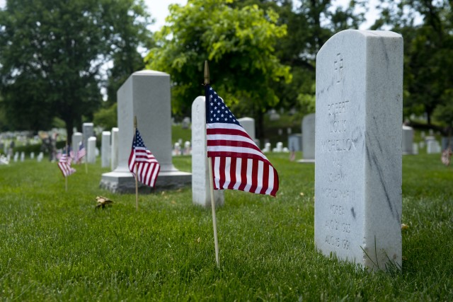 Old Guard Soldiers honor fallen with flags at Arlington graves
