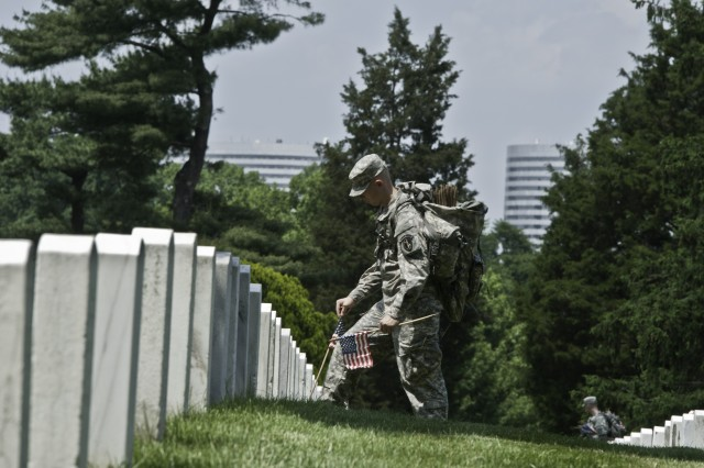 "Soldiers from the 3d U.S. Infantry Regiment (The Old Guard) place flags in front of the gravesites in Arlington National Cemetary, Va., May 22, 2014, during ""Flags In""."