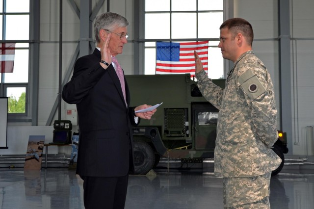 Secretary of the Army John M. McHugh (left) re-enlists Michigan Army National Guard Spc. Daniel Welburn, May 20, 2014, at Lielvarde Air Base, Latvia. Welburn is in Latvia with the Michigan-based Shadow RQ-7B UAV Platoon, working with Latvian Armed Forces. The Latvian military is providing aviation tower and runway support, while the Michigan National Guard flight crew operated, maintained, and supported the aircraft.  These training exercises are a continuation of the 22-year state partnership between Michigan and the Republic of Latvia.