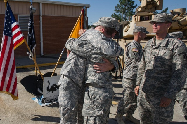 "Sgt. Thomas Evans (left), a native of Trenton, N.J., and an infantryman with Company B, 1st Battalion, 64th Armor Regiment ""Desert Rogues"", 2nd Armored Brigade Combat Team, 3rd Infantry Division, embraces one of his fellow Bayonet Brothers, here at the Rogues' motor pool, May 16. Evans was just awarded the Bronze Star Medal with 'V' device for Valor for his actions in combat during his last deployment to Afghanistan with the Rogues, which took place from March to December of 2012. (U.S. Army photo by Sgt. Richard Wrigley, 2nd ABCT, 3rd ID, Public Affairs NCO)"