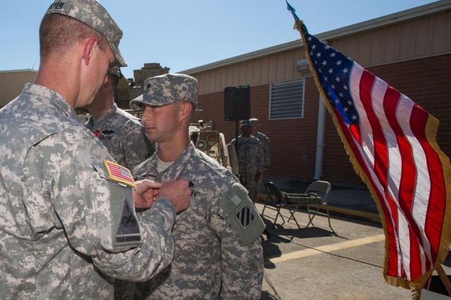 "Lt. Col. Sean Kuester, commander, 1st Battalion, 64th Armor Regiment ""Desert Rogues"", 2nd Armored Brigade Combat Team, 3rd Infantry Division, awards Spc. Dustin Smothers,a native of Jasper, Ala., and an infantryman with Company B, 1-64th AR, the Bronze Star Medal with 'V' device for Valor here at the Rogues' motor pool, May 16. Smothers was awarded the BSM with 'V' device for his heroic actions in combat during their last deployment to Afghanistan with the Rogues, which took place from March to December of 2012. (U.S. Army photo by Sgt. Richard Wrigley, 2nd ABCT, 3rd ID, Public Affairs NCO)"