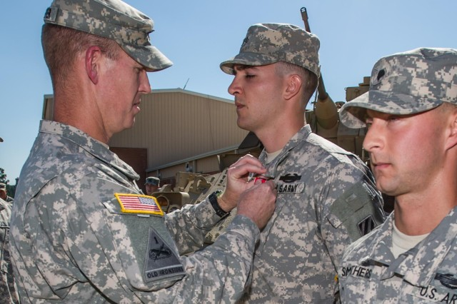 "Lt. Col. Sean Kuester, commander, 1st Battalion, 64th Armor Regiment ""Desert Rogues"", 2nd Armored Brigade Combat Team, 3rd Infantry Division, awards Sgt. Thomas Evans, a native of Trenton, N.J., and an infantryman with Company B, 1-64th AR, the Bronze Star Medal with 'V' device for Valor here at the Rogues' motor pool, May 16. Evans was awarded the BSM with 'V' device for his heroic actions in combat during their last deployment to Afghanistan with the Rogues, which took place from March to December of 2012. (U.S. Army photo by Sgt. Richard Wrigley, 2nd ABCT, 3rd ID, Public Affairs NCO)"