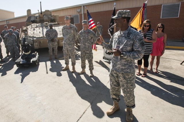 """Capt. Brian Kitching (right), the former commander of Company B, 1st Battalion, 64th Armor Regiment """"Desert Rogues"""", 2nd Armored Brigade Combat Team, 3rd Infantry Division, speaks to those in attendance about Sgt. Thomas Evans, a native of Trenton, N.J., and Spc. Dustin Smothers, a native of Jasper, Ala., both infantryman of the Bayonet Company, after they were both awarded the Bronze Star Medal with 'V' device for Valor here at the Rogues motor pool, May 16. Both Soldiers were awarded the BSM with 'V' device for their individual actions on separate occasions in combat during their last deployment to Afghanistan with the Rogues, which took place from March to December of 2012. Kitching was commander of the Bayonets during this period, and was also in the same battle in which Evans fought with distinction. (U.S. Army photo by Sgt. Richard Wrigley, 2nd ABCT, 3rd ID, Public Affairs NCO)"""