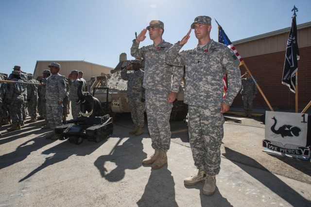 "Sgt. Thomas Evans (middle), a native of Trenton, N.J., and Spc. Dustin Smothers (right), a native of Jasper, Ala., both infantryman with Company B, 1st Battalion, 64th Armor Regiment ""Desert Rogues"", 2nd Armored Brigade Combat Team, 3rd Infantry Division, salute as the flag is lowered during ""To the Colors"", here at the Rogues' motor pool, May 16. Both Soldiers were just awarded the Bronze Star Medal with 'V' device for Valor for their individual actions on separate occasions in combat during their last deployment to Afghanistan with the Rogues, which took place from March to December of 2012. (U.S. Army photo by Sgt. Richard Wrigley, 2nd ABCT, 3rd ID, Public Affairs NCO)"