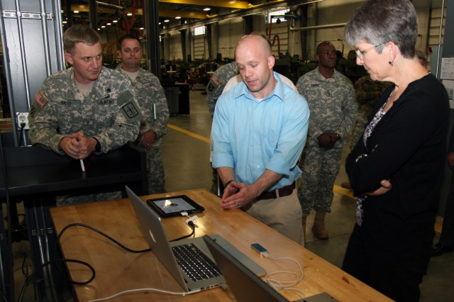 David Garrison, Combined Arms Support Command Technology Integration Branch instructional design specialist, center, explains to Terry Gerton, Veteran's Employment and Training Service deputy assistant secretary for policy, some of the applications created for mobile devices during a May 20 tour. The apps enable students to enhance their training in a variety of subjects from their mobile, gaming and wireless devices. (U.S. Army photo by Keith Desbois)