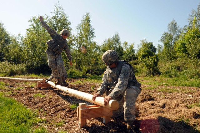 ROSE BARRACKS, Germany -- Troopers assigned to the 2d Cavalry Regiment assist a team mate walk on a log May 20, 2014, at Grafenwoehr, Germany. The Troopers competed during the Dragoon Challenge, an event that tested their teamwork and physical fitness.