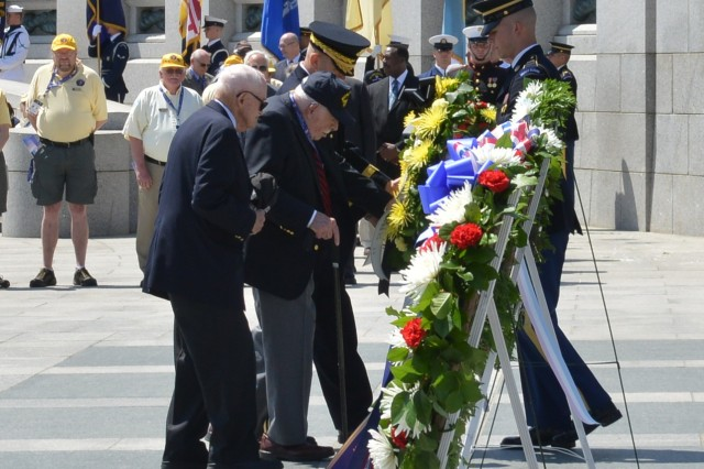 World War II veterans Robert Quenkin, (center)51st Combat Engineer Battalion, Utah Beach, Normandy, and Alan Kukens, a member of the 20th Armor Division, that liberated the Nazi death camp Dachau, are escorted by Maj. Gen. Jeffrey S. Buchanan, U.S. Army Military District of Washington's commanding general at a wreath laying during the WWII Memorial's 10th anniversary held at the WWII Memorial, Washington D.C., May 24, 2014.
