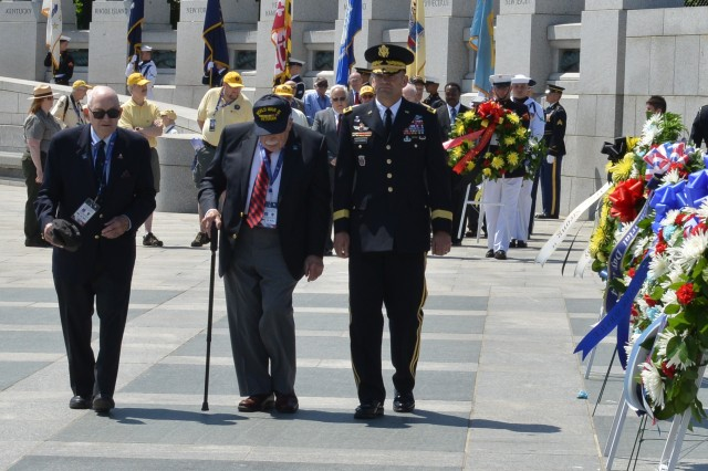 World War II veterans Robert Quenkin (center), 51st Combat Engineer Battalion, Utah Beach, Normandy, and Alan Kukens, a member of the 20th Armor Division, that liberated the Nazi death camp Dachau, are escorted by Maj. Gen. Jeffrey S. Buchanan, U.S. Army Military District of Washington's commanding general during a wreath laying at the WWII Memorial's 10th anniversary, Washington D.C., May 24, 2014.