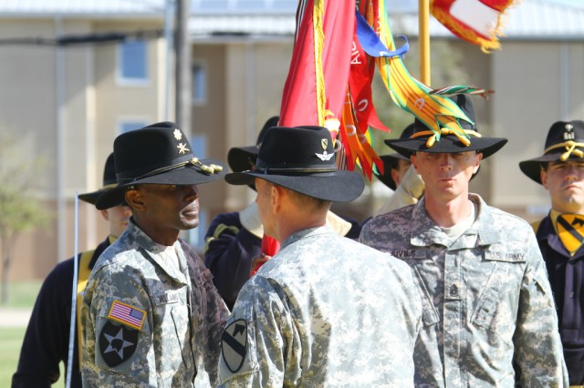 Col. Cory Mendenhall, commander of 1st Air Cavalry Brigade, 1st Cavalry Division, passes the colors of 1st Battalion, 21st Field Artillery Regiment, Task Force Pegasus Fires, to Maj. Everett Williams, the executive officer of 1-21st FAR, during a relinquishment of command ceremony at Fort Hood, Texas, April 10. Lt. Col. Kenneth McDaniel relinquished command of 1-21st FAR as the battalion prepares for inactivation (U.S. Army photo by Sgt. Garett Hernandez, Task Force Pegasus Fires Public Affairs).