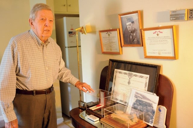 Charles Maupin, a veteran of World War II with the 29th Infantry Division, shows his memorabilia from World War II and D-Day. He has numerous medals and a display containing rocks and sand from Normandy's Omaha Beach.