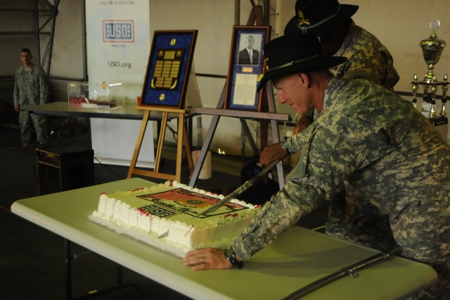 "ROSE BARRACKS, Germany -- Colonel D. A. Sims (right), commander of 2d Cavalry Regiment, and Command Sgt. Maj. Wilbert E. Engram Jr. (middle), senior enlisted advisor for the Regiment, cut a cake with a saber in celebration of the Week of The Dragoon May 22, 2014, at Vilseck Army Airfield, Germany. The two cut the cake during a ""Dragoons Got Talent"" competition at the end of the celebration."