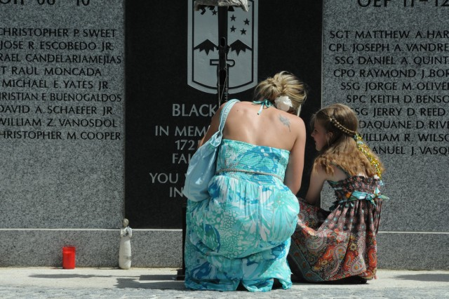 Judy Craig and her daughter, Leona, kneel before the 172nd Infantry Brigade memorial after the Memorial Day ceremony in Tower Barracks. The Craigs, a Gold Star Family, lost their husband and father, Staff Sgt. Heathe Nathanniel Craig, in Afghanistan in 2006.