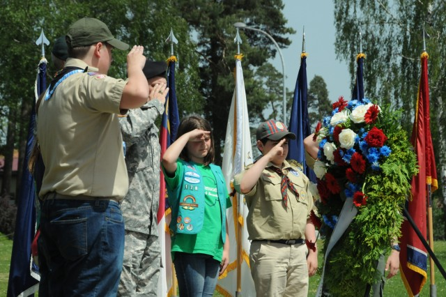 Representatives from the Girl and Boy Scouts of America, along with U.S. Army Garrison Bavaria Commander Col. James Saenz, salute a memorial wreath honoring fallen Soldiers during the Memorial Day ceremony on Tower Barracks, May 22.