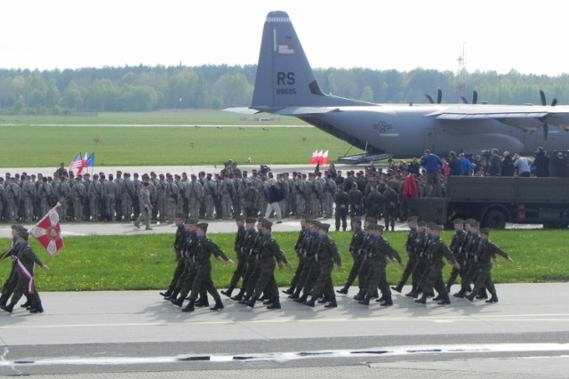 Paratroopers from the Vicenza, Italy-based 173rd Airborne Brigade, pictured in the background, arrive in Poland, April 23, 2014, to begin a training rotation with the Polish army's 6th Airborne Brigade. Making sure all 173rd paratroopers and equipment items were accounted for, loaded up and headed to training areas were Soldiers from U.S. Army Europe, G-4 Section (Logistics), and the 21st Theater Sustainment Command, Special Operations, Transportation Integration Branch.