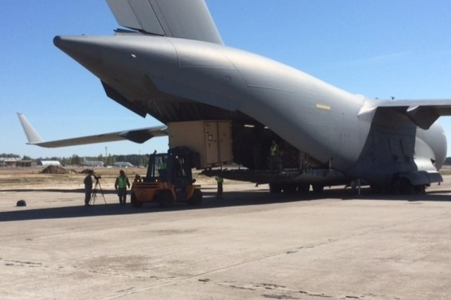 A forklift driver unloads a container of equipment from a C-17 in Lithuania, shortly after the arrival of more than 130 paratroopers from the 173rd Airborne Brigade, April 24, 2014. The U.S. paratroopers are scheduled to conduct multinational training activities with their counterparts from the Lithuanian army over the next few months. Making sure all 173rd paratroopers and equipment items were accounted for, loaded up and headed to training areas were Soldiers from U.S. Army Europe, G-4 Section (Logistics), and the 21st Theater Sustainment Command, Special Operations, Transportation Integration Branch.
