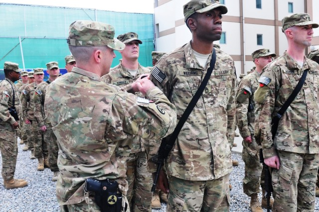 Sgt. 1st Class Garrick Williams, water supply sergeant with the 3rd Sustainment Command (Expeditionary), receives his combat patch from Capt. Adam Vogel, the 3rd ESC's Headquarters and Headquarters Company commander, during a ceremony at New Kabul Compound, Afghanistan, May 24.
