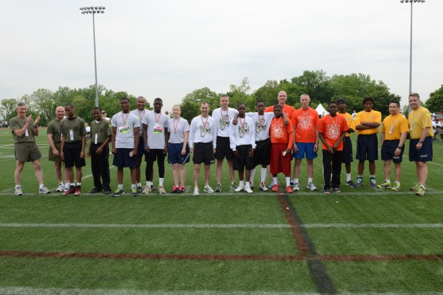 Service members and Special Olympics sprinters stand for a group photo during Military Day at the annual Special Olympic summer games hosted by Special Olympics D.C., at the Catholic University in Washington, D.C., May 21, 2014.