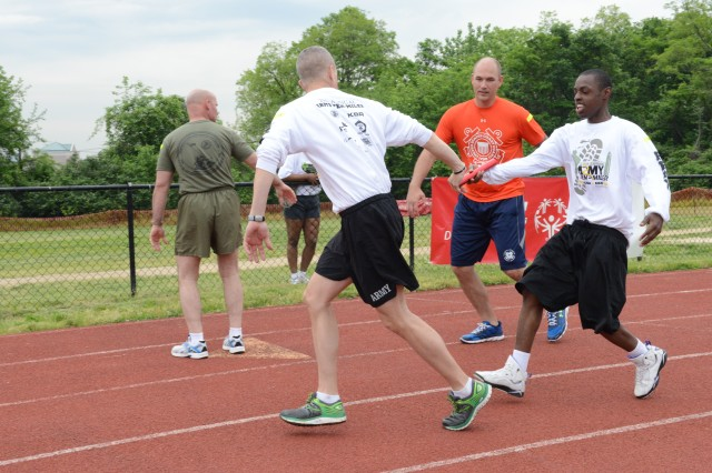 Command Sgt. Maj. David O. Turnbull, Joint Force Headquarters -- National Capital Region/U.S. Army Military District of Washington senior enlisted advisor, grabs the baton from Demarcus Cutchin, Special Olympics sprinter during the 4 x 100 meter relay race at the annual Special Olympic summer games hosted by Special Olympics D.C. at the Catholic University in Washington, D.C., May 21, 2014.