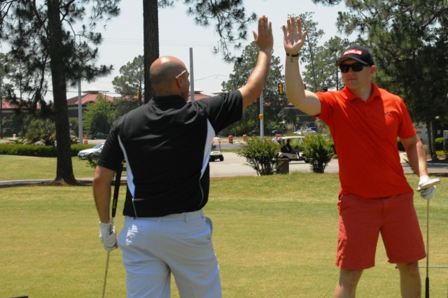 Capt. Orlando Varela (left), from Charlestown, S.C., and the Headquarters and Headquarters Company commander for 4th Infantry Brigade Combat Team, 3rd Infantry Division, and Capt. Hugh Pearce, from Dublin, Ga., the company's executive officer, high five after Varela putted in for a birdie during the Vanguard Brigade's staff golf scramble, May 22, 2014, on Fort Stewart, Ga. The friendly tournament boosted morale and camaraderie among the sections during the competition. (U.S. Army Photo by Staff Sgt. Elvis Umanzor, 4th IBCT, 3rd ID, Public Affairs)