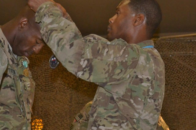 U.S. Army Sgt. 1st Class Jerry Delva, right, assigned to the 311th Sustainment Command (Expeditionary) dons the Sergeant Audie Murphy Club (SAMC) medallion onto Sgt. 1st Class Dwayne Taylor, a senior fuel operations sergeant with Headquarters and Headquarters Company, 3rd Sustainment Brigade, during a SAMC induction ceremony at Kandahar Airfield, Afghanistan, June 13, 2013. The SAMC is a private U.S. Army organization, which recognizes exceptional Noncommissioned officers who show exemplary leadership traits. (U.S. Army photo by Spc. Rochelle Krueger/Released)