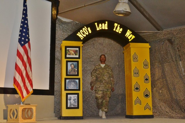 Staff Sgt. Natalie Williams, the noncommissioned officer in charge of the strength management section with Headquarters and Headquarters Company, 3rd Sustainment Brigade, walks through the NCO arch as she is inducted into the Sergeant Audie Murphy Club, June 13, at Kandahar Airfield, Afghanistan.  (U.S. Army photo by Spc. Rochelle Krueger, 3rd Sustainment Brigade Public Affairs)