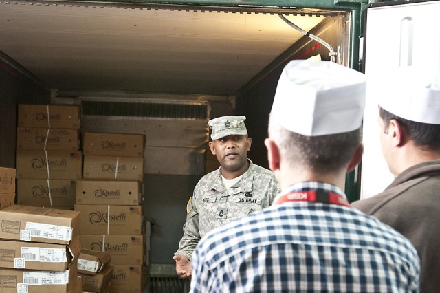 Sgt. 1st Class Michael E. Gee, Task Force Medical food handler class instructor, talks about food storage during a tour of the dining facility on Camp Bondsteel, Kosovo, May 19, 2014. Task Force Medical's force health protection team is working with the Kosovo food inspectors to help develop their own food safety program.