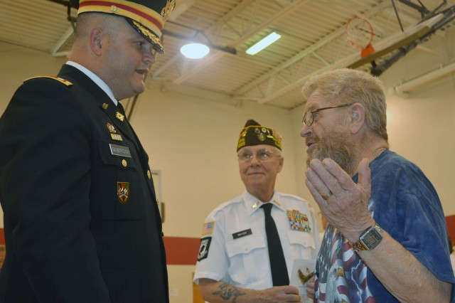 Commander Paul Mayer (center), American Legion Post 148,  looks on as Lt. Col. Frank Gilberston,  Army Sustainment Command,  speaks with Vietnam veteran James Ritter following the Memorial Day ceremony in Savanna, Ill., May 26. Ritter served in the Army from 1967 to 1969.