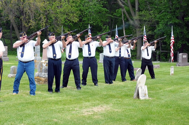The American Legion Post 532 Honor Guard conducts a rifle salute prior to the playing of Taps by Rich Atwood, a member of American Legion Post 26 in Davenport.