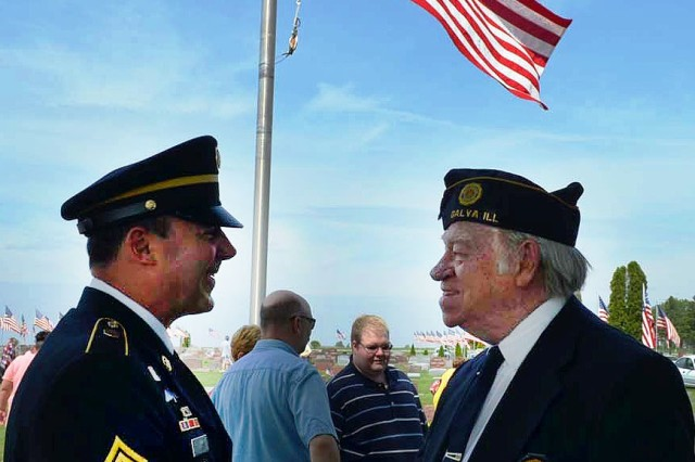 Wade Abbott, commander of American Legion Post 45, talks with Sgt. Maj. Douglas Martin, U.S. Army Sustainment Command following the Memorial Day ceremony in Galva, Ill., May 26.