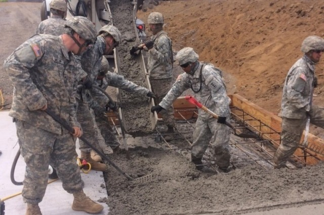 Soldiers with the 561st Engineer Company (Horizontal), 84th Engineer Battalion, 130th Engineer Brigade, 8th Theater Sustainment Command, pour concrete to improve roadways at the Pohakuloa Training Area, Hawaii, during the unit's 60-day training and construction mission, April 1 through June 1.