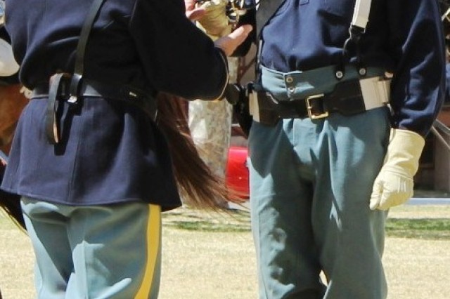 From left, Col. Thomas Boone, U.S. Army Garrison commander, gives Chaplain (Lt. Col.) Glen McFarland a pair of brass spurs upon his graduation from B Troop -- 4th Regiment, U.S. Cavalry (Memorial) riding school May 22 on Brown Parade Field. In addition to receiving the spurs and a certificate, the three new B Troop riders participated in an open-field pistol charge earlier in the ceremony.