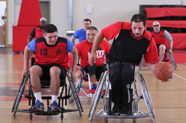 Warrior Transition Battalion-Europe Soldier Spc. Israel Cruz chases Bundesliga FCK Rolling Devils wheelchair basketball player Sascha Gergele down the court during a friendly game at the Kleber Kaserne Fitness Center May 30.
