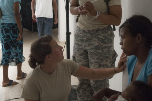 Cadet Kezia R. Constant, a native of Hadley, Mass., and a member of Georgetown University Hoya Battalion, interprets between a local patient and Spc. Lytecia Moody, a native of Vacaville, Calif., with the 352nd Combat Support Hospital Battalion out of Camp Parks in Dublin, Calif., at the Medical Readiness Training Exercise in Paraiso, Barahona. The MEDRETE is here as part of the Beyond the Horizon 2014 mission to build schools and clinics and provide medical care for the local residents of the Dominican Republic. (U.S. Army photo by Sgt. Lindsey Schulte, 364th Press Camp Headquarters, Task Force Larimar)