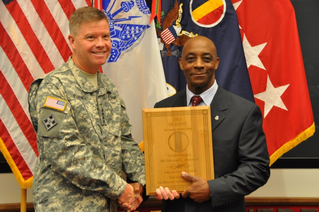 Michael Armstead, the Army's Civilian Instructor of the Year, stands with Gen. David Perkins, the commanding general of U.S. Army Training and Doctrine Command, during TRADOC's Instructor of the Year Ceremony at the Morelli Auditorium, on Fort Eustis, Va., May 30, 2014.