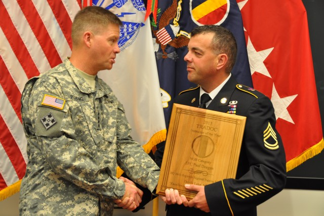 Sgt. 1st Class Paul Deegan, the National Guard Instructor of the Year, stands with Gen. David Perkins, the commanding general of U.S. Army Training and Doctrine Command, during TRADOC's Instructor of the Year Ceremony at the Morelli Auditorium, on Fort Eustis, Va., May 30, 2014.