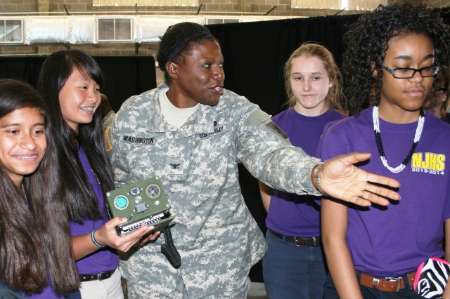 Col. Washington explains to Nolan Richardson Middle School students the technological advances contained within one hand-held radio during a tour of the Network Integration Evaluation 14.2.