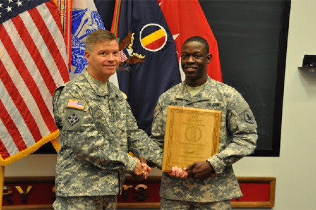 Staff Sgt. Sony Merus, the Army's Non-Commissioned Officer Instructor of the Year, stands with Gen. David Perkins, the commanding general of U.S. Army Training and Doctrine Command, during TRADOC's Instructor of the Year Ceremony at the Morelli Auditorium, on Fort Eustis, Va., May 30, 2014.