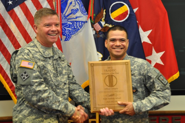 Chief Warrant Officer 2 Juan Jusino, the Army's Warrant Officer Instructor of the Year, stands with Gen. David Perkins, the commanding general of U.S. Army Training and Doctrine Command, during TRADOC's Instructor of the Year Ceremony at the Morelli Auditorium, on Fort Eustis, Va., May 30, 2014.