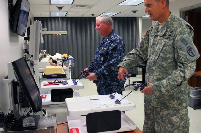 Brig. Gen. Dennis Doyle, commanding general for Pacific Regional Medical Command and Tripler Army Medical Center, in Honolulu, along with Navy Capt. Andrew Findley, TAMC deputy commander of Clinical Services, interact with a fundamentals of laparoscopic trainer system, which allows surgical residents and practicing surgeons to develop psychomotor skills and dexterity required in basic laparoscopic surgery skills, during an open house for the Medical Simulation Center, May 27, 2014.