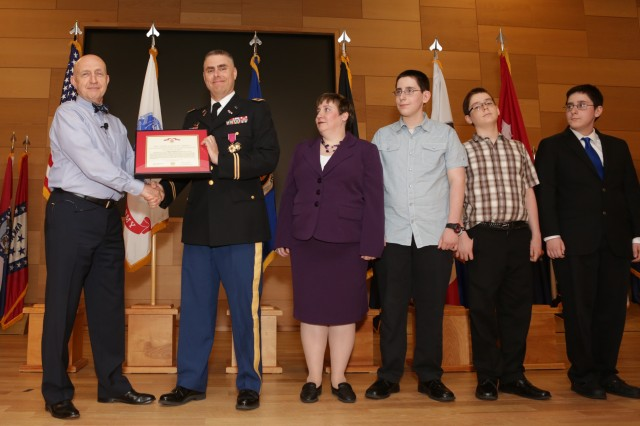 Maj. Gen. Nickolas G. Justice (R) (left), former program executive officer for Command, Control and Communications-Tactical (PEO C3T), presents Col. Jonas Vogelhut (center) with the Legion of Merit award during Vogelhut's retirement ceremony on May 30.  Mrs. Paula Vogelhut and their triplet sons (left to right), Marc, Jeremiah and Samuel look on.