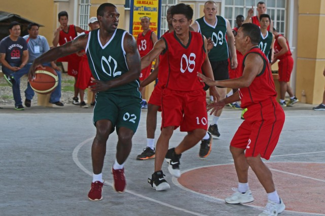 Philippine and U.S. soldiers duke it out during a basketball tournament May 5 between Philippine and U.S. soldiers in Palayan City, Philippines, as part of Balikatan 2014, a bilateral training exercise between Philippine and U.S. service members. Balikatan is designed to improve cooperation and interoperability between the two nations' armed forces through training, as well as humanitarian aid and disaster relief projects. Activities such as the basketball tournament allow for increased cohesion between Philippine and U.S. forces. Philippine soldiers are assigne to the 20th Infantry Battalion, 8th Infantry Division, and U.S. soldiers are assigned to the 25th Infantry Division. (U.S. Marine Corps photo by Lance Cpl. Shaltiel Dominguez)