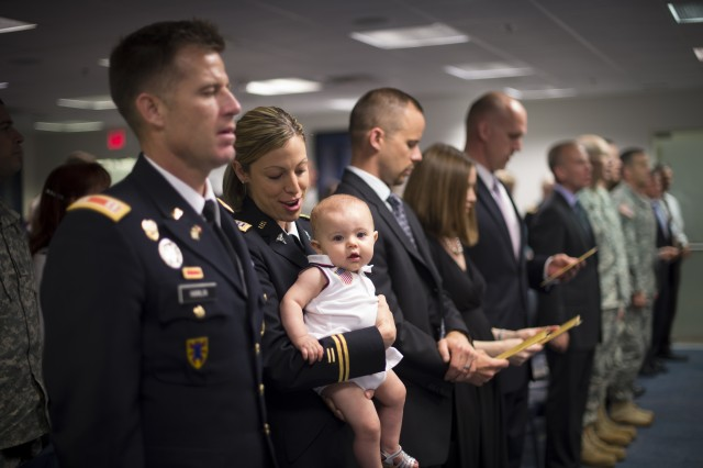 Capt. Lauren M. Hamlin, a recent recipient of the Pace Award, holds her baby as she and the audience sing The Army Song at the Pentagon, June 3, 2014. Hamlin developed and implemented cost-saving strategies on multiple Army contracts that saved the Army more than $14.7 million. She also single handedly developed the capability for the Comprehensive Soldier and Family Fitness Program Training Center managers and program managers Army-wide to order training and information materials online, partnering with the Defense Logistics Agency to save more than $880,000.