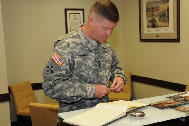Gen. David G. Perkins signs the visitors book on his first trip to Army Materiel Command headquarters at Redstone Arsenal, Ala., June 3, 2014.