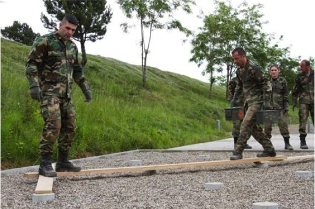 Using wooden two-by-fours, members of the Kosovo Security Force carry supplies across an imaginary minefield during a Leadership Reaction Course at the KSF Training and Doctrine Command compound in Ferizaj, May 29, 2014. The course is designed to challenge the members by confronting them with unique obstacles, and forces them to work as a team and think outside the box.
