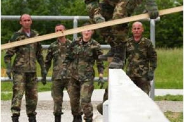 A non-commissioned officer in the Kosovo Security Force carries a wooden two-by-four across a balance beam during a Leadership Reaction Course at the Kosovo Security Force Training and Doctrine Command compound in Ferizaj, Kosovo, May 29, 2014. If anything touched the ground below, the team would have to restart the obstacle.