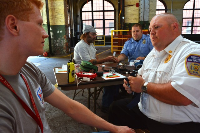 Arsenal Fire Chief John Whipple, right, getting ready to check the blood pressure of Machinist Robert Seeloff.